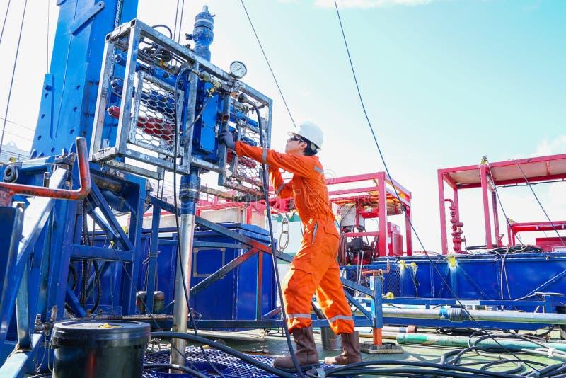 De booreilandarbeider inspecteren en de vestigings hoogste zijhulpmiddelen eerst voor veiligheid aan van het perforatieolie en ga stock foto's