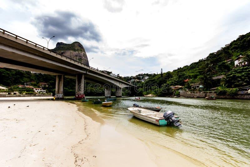 de boot anrchored onderaan brug in het punt waar het overzees de Marapendi-Lagune, in Barra da Tijuca, Rio de Janeiro ontmoet stock foto's