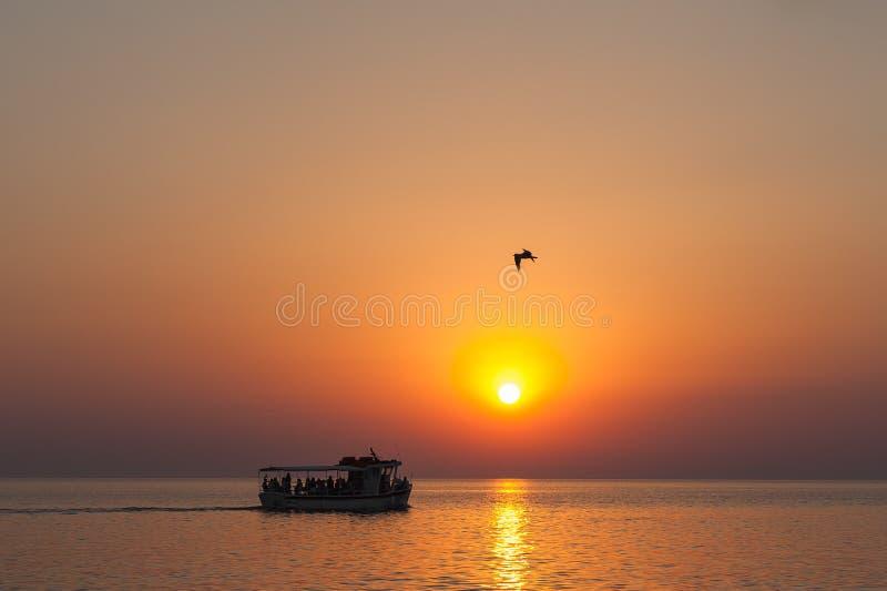 De boot bij zonsondergang, met toeristen bij zonsondergang, zwemt onder de schroeiende zon, een fabelachtige overzeese zonsonderg royalty-vrije stock foto's
