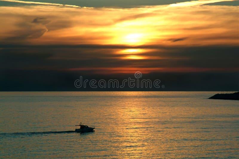 De boot die van de recreatie bij zonsondergang vaart stock foto's