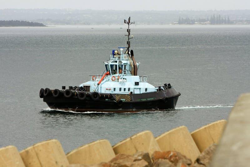 De boot die van de sleepboot naar overzees gaat stock foto