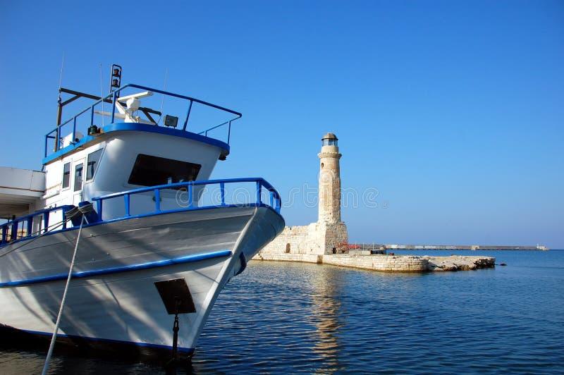 De boot en de vuurtoren, Cyprus stock afbeelding