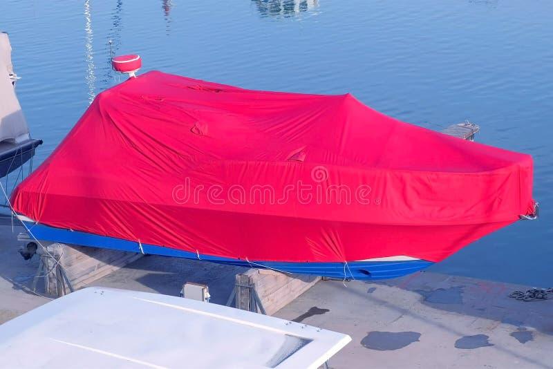 De boot met rood geteerd zeildoek in de zeehaven wordt behandeld wordt geparkeerd op de pijler die royalty-vrije stock afbeeldingen