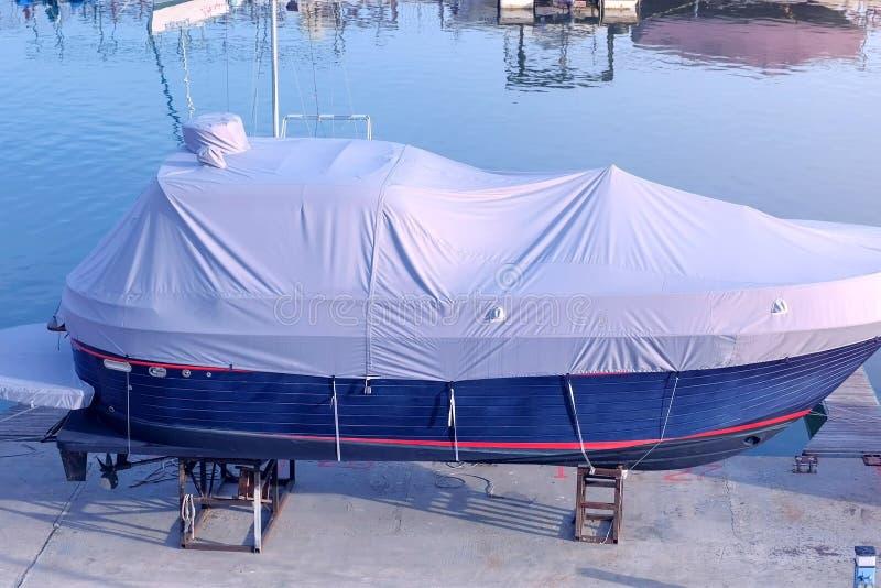 De boot met wit geteerd zeildoek in de zeehaven wordt behandeld wordt geparkeerd op de pijler die stock afbeeldingen