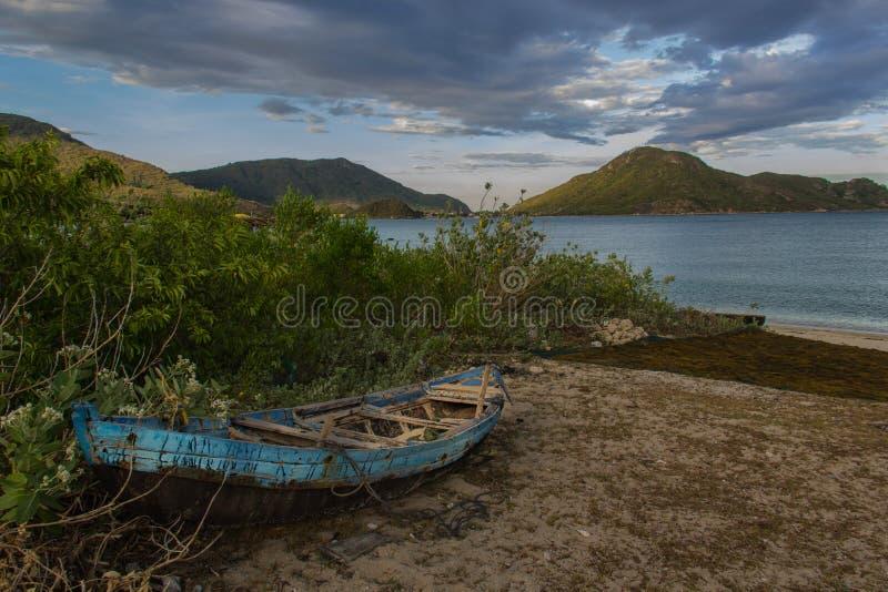 De boot van de oude visser op het tropische strand stock foto's