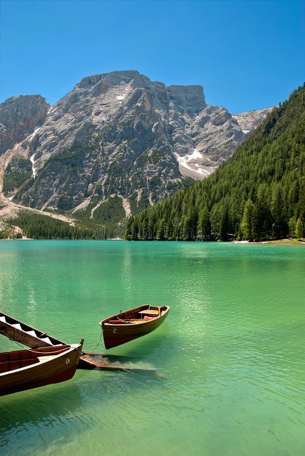 De boot van de rij op een meer met bergen in hij achtergrond stock afbeelding