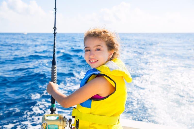 De boot van het jong geitjemeisje visserij het met een sleeplijn vissen staafspoel en geel reddingsvest stock afbeelding