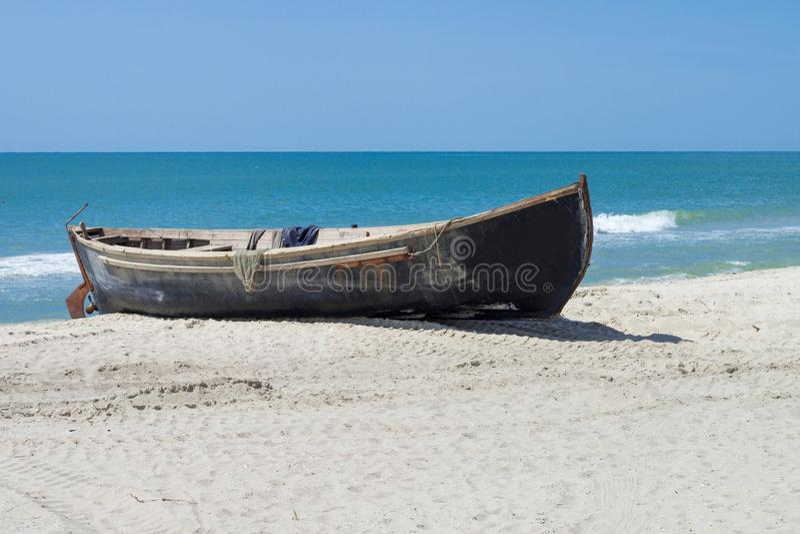 De boot van de kleine houten visser met visnetten die op wit zandig strand dichtbij sealine drogen royalty-vrije stock foto's