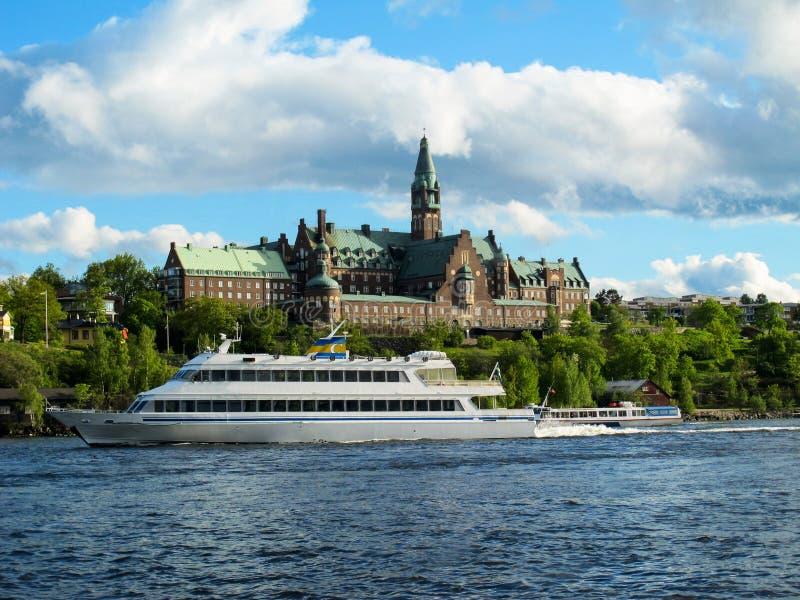 De boot van de toeristencruise drijft op het blauwe water van het meer op de achtergrond van de mooie gebouwen van Stockholm royalty-vrije stock fotografie