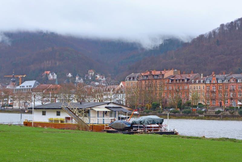De boot verankerde permanent bij de de rivierweide van Neckar dichtbij stadscentrum van Heidelberg, met oude gebouwen en mooie he stock afbeeldingen