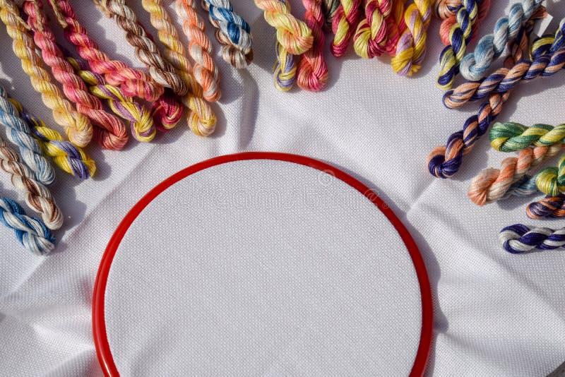 De borduurwerkhoepel met canvas en gekleurde naaiende draden stock foto's