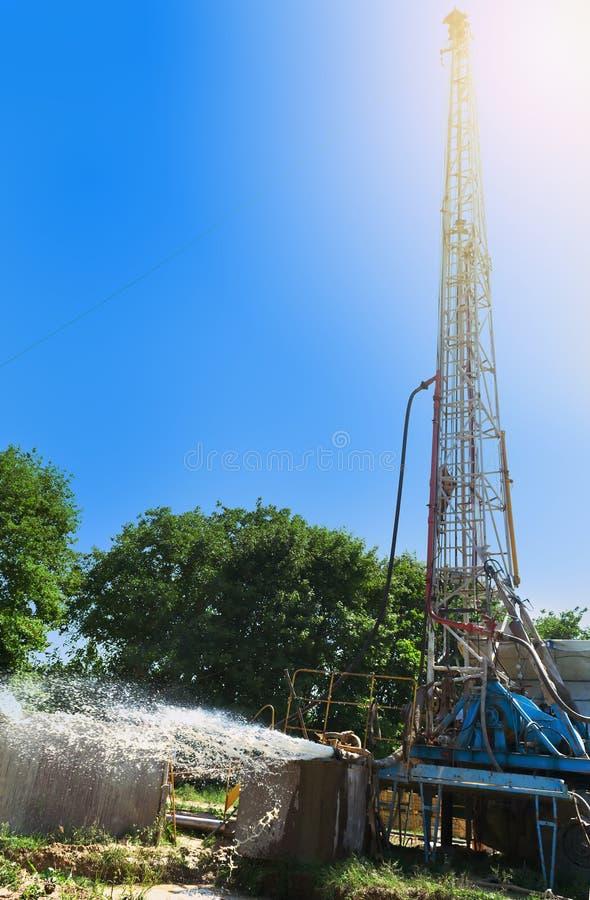 De boringsinstallatie boort een put om water te halen Goed assimilatiewatervoorziening onder rotsdruk aan de oppervlakte stock afbeelding