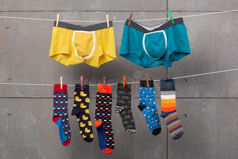 De borrels van twee mensen en vele gekleurde sokken hangen op de kabels, alsof drogend na was, concept, op een grijze achtergrond stock foto