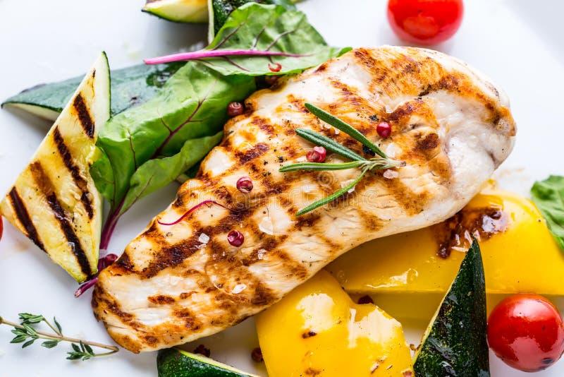 De borst van de grillkip roosterde groenten met kippenborst Geroosterde kip met groenten op eiken lijst stock fotografie