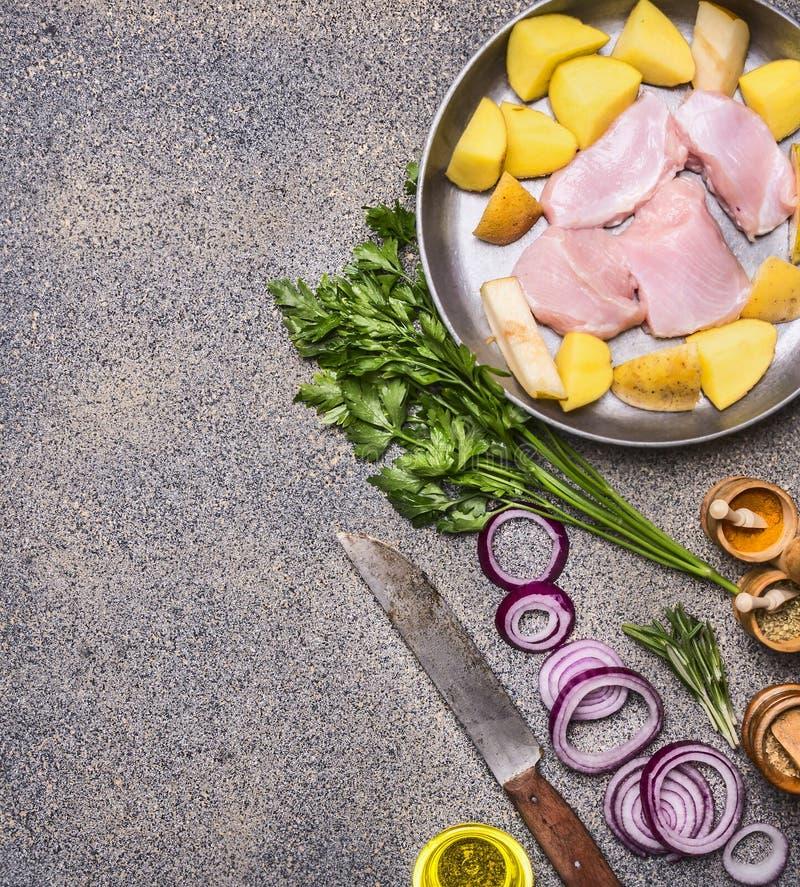 De borst van Turkije met peren en aardappels op een uitstekende pan met rode ui en kruiden met mes voor vlees en diverse kruiden  stock foto