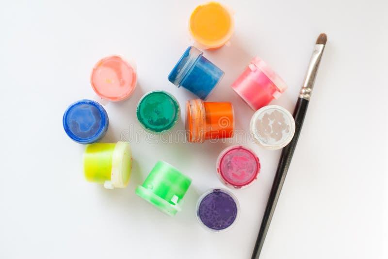 De borstel en een reeks van multicolored gouache op een witte achtergrond hoogste meningsvlakte lagen stock afbeeldingen