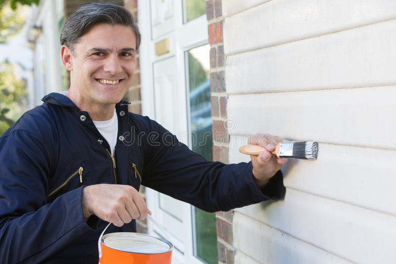 De Borstel en Tin Painting Outside Of House van de mensenholding royalty-vrije stock foto's