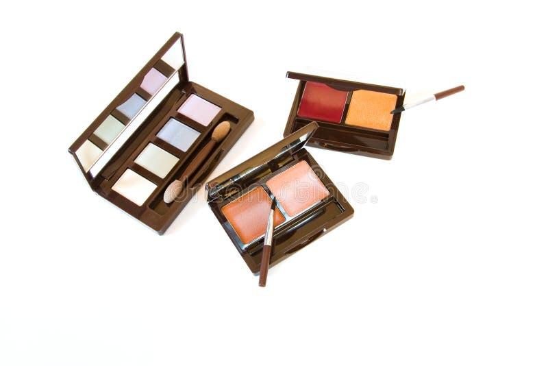 Make-upborstel en kleurrijke schoonheidsmiddelen stock foto