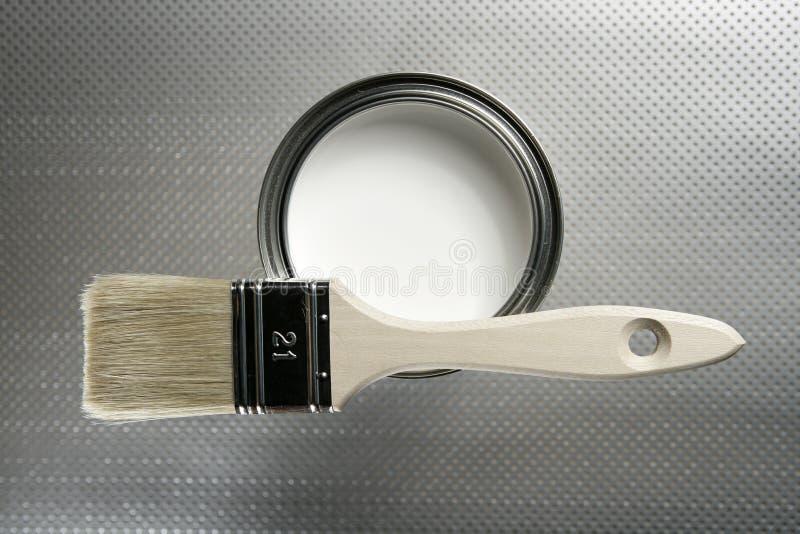 De borstel van de schilder en wit verftin stock afbeeldingen