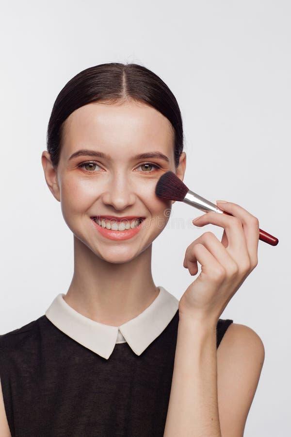 De borstel van de de holdingsmake-up van de make-upkunstenaar stock foto