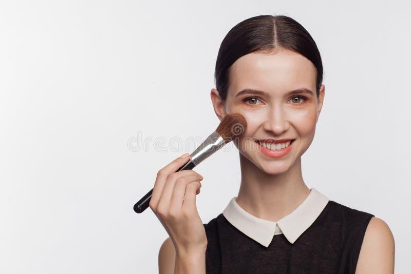 De borstel van de de holdingsmake-up van de make-upkunstenaar stock foto's