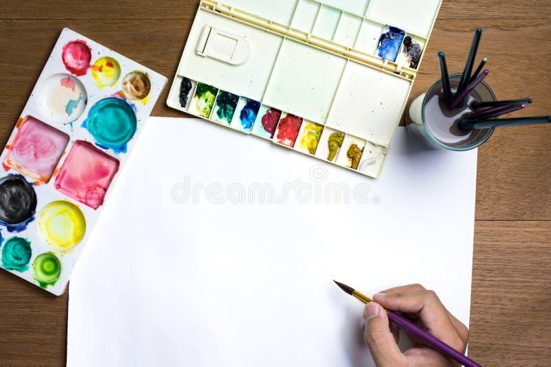 De borstel van de de holdingsverf van de mensenhand op Witboek met kleurrijke waterverf en materiaal op houten achtergrond royalty-vrije stock afbeeldingen