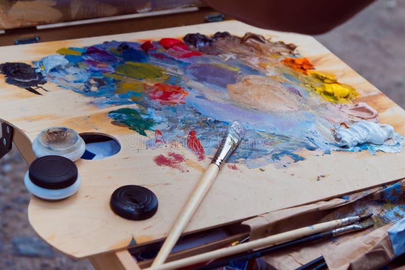De borstel van de schilder, met verschillende heldere kleurenverven wordt bevlekt, rust na plainair het schilderen zitting die royalty-vrije stock afbeeldingen