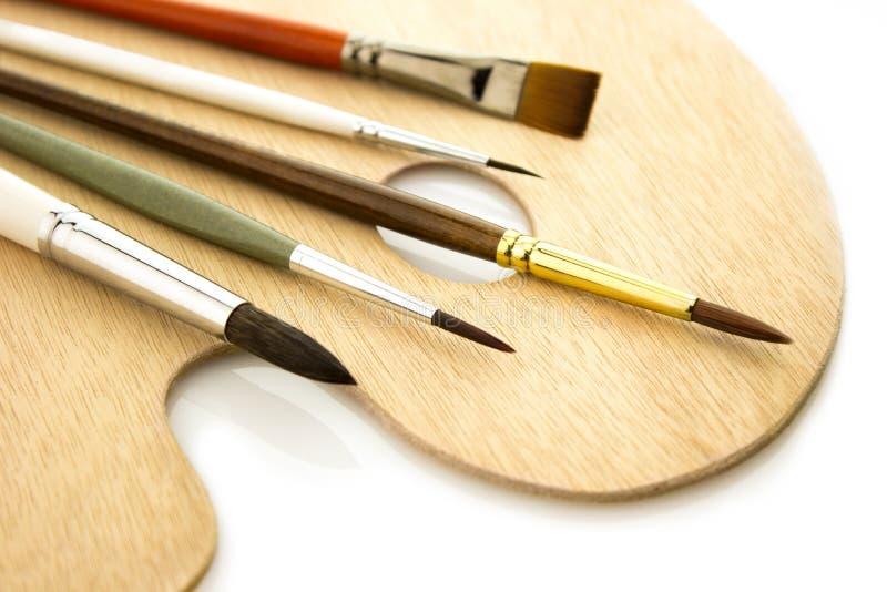 De borstels van de kunstkleur op geïsoleerd woodepalet royalty-vrije stock afbeeldingen