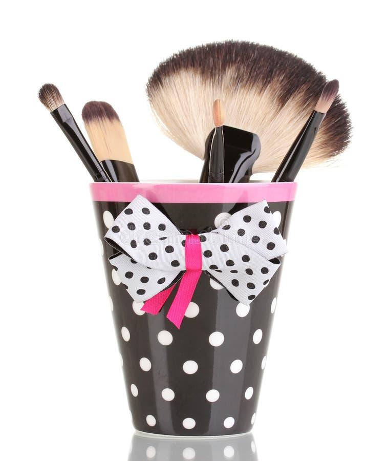 De borstels van de make-up in zwarte een polka-punt kop stock fotografie