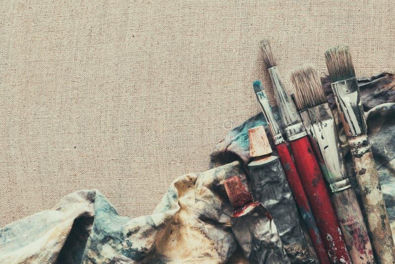De borstels van de kunstenaarsverf, de close-up van verfbuizen op linnencanvas stock afbeeldingen