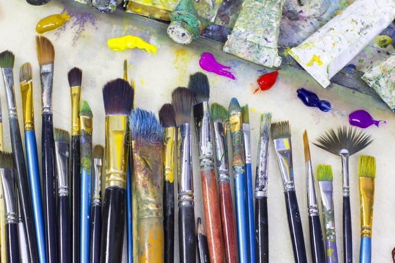 De borstels voor het schilderen en de gekleurde olieverven liggen op palet in de kunstenaars` s studio stock afbeelding