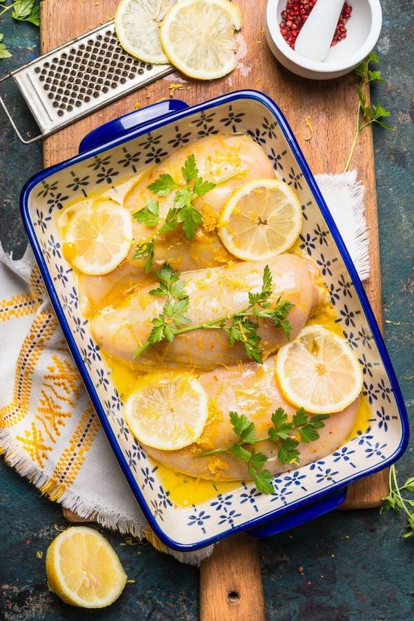 De borstvoorbereiding van de citroenkip Bakselschotel met Citroenkip op keukenlijst met ingrediënten en kokende hulpmiddelen, hoo stock afbeeldingen