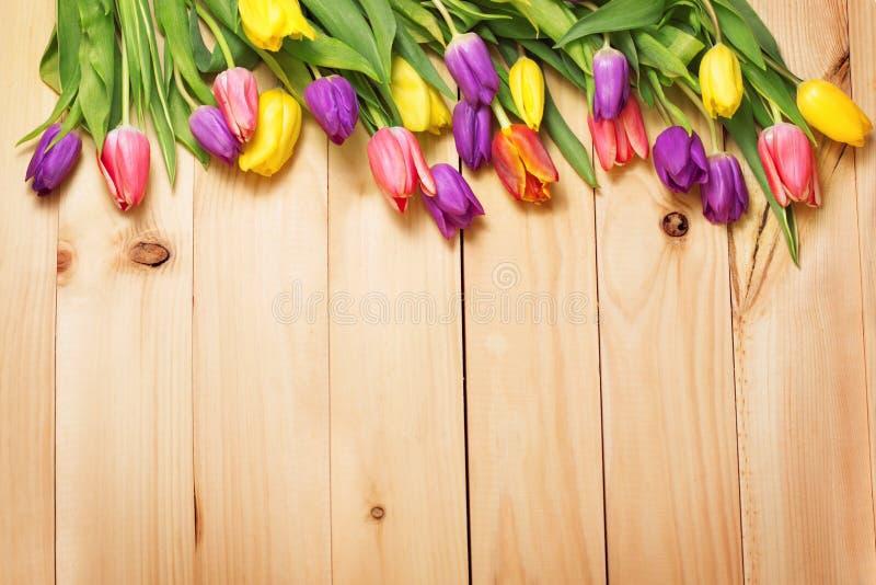 De bos van de lentebloemen bij houten vloertextuur Mooie Tulpenbou royalty-vrije stock fotografie