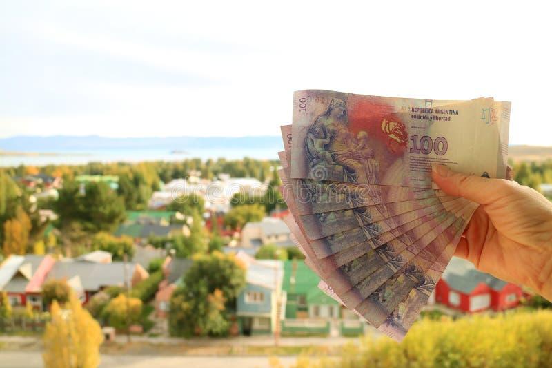 De Bos van de de Handholding van het wijfje van Argentijnse 100 Peso'srekeningen terug met de Onscherpe Stad van Gr Calafate op A royalty-vrije stock afbeelding