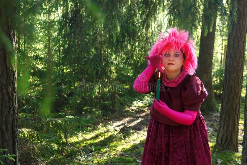 De bosheks in purpere kleren tovert onder het bos met kaarsen Verticale foto royalty-vrije stock fotografie