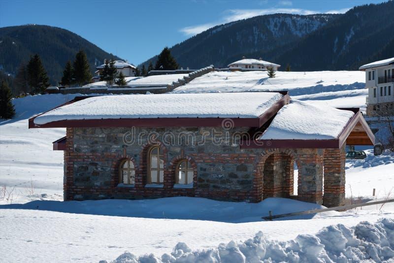 De bosscène van de winter Kleine kapel bij de berg in een zonnige de winterdag Sneeuwfairytale in Bulgarije royalty-vrije stock afbeeldingen