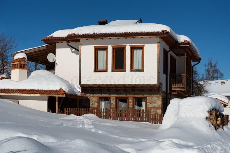 De bosscène van de winter Plattelandshuisje bij de berg in een zonnige de winterdag Sneeuwfairytale in Bulgarije royalty-vrije stock foto