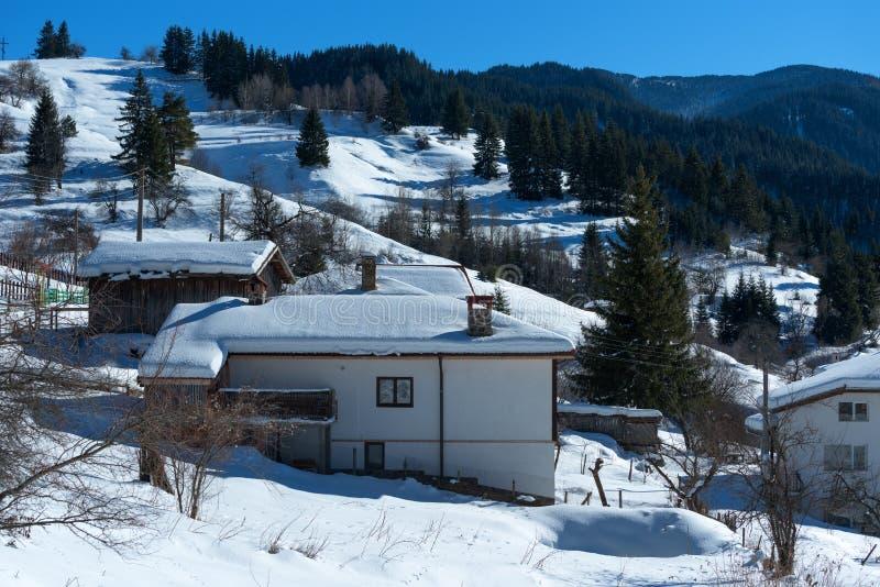 De bosscène van de winter Plattelandshuisjes bij de berg in een zonnige de winterdag Sneeuwfairytale in Bulgarije royalty-vrije stock afbeeldingen