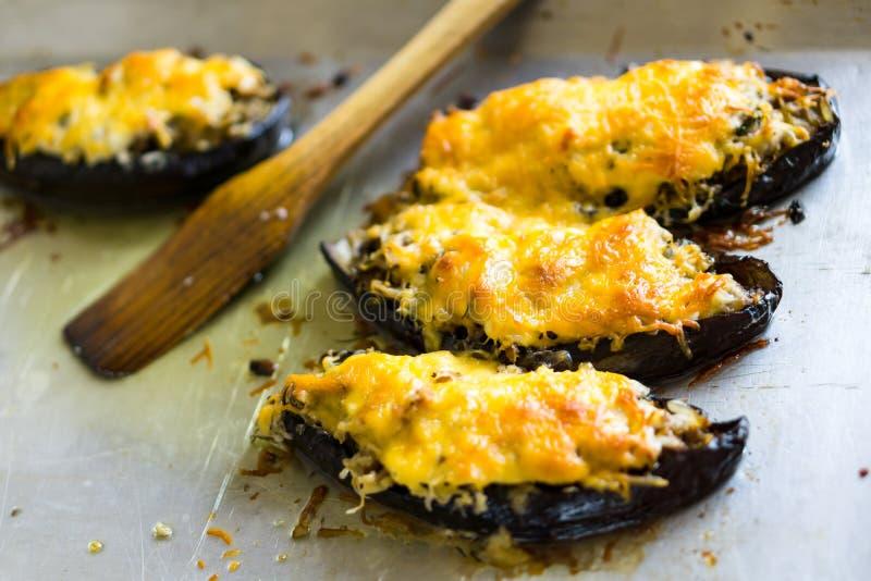 De boten van auberginecourgette vulden met vlees, rijst, tomaat en paddestoelen met geraspte kaas stock foto's