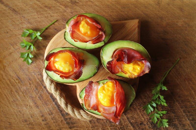 De Boten van het avocadoei met bacon op donkere houten achtergrond Hoogste mening royalty-vrije stock afbeeldingen