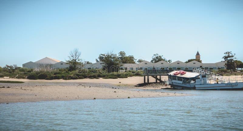 De boten van het toeristenvervoer legden in de lagunes van Ria Formosa Natural Park vast dichtbij de haven van Tavira, Portugal stock afbeelding