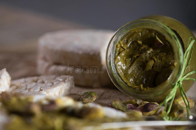 De boter van de pistachenoot die op een plak van rijstkn?ckebrood wordt afgeroomd stock fotografie