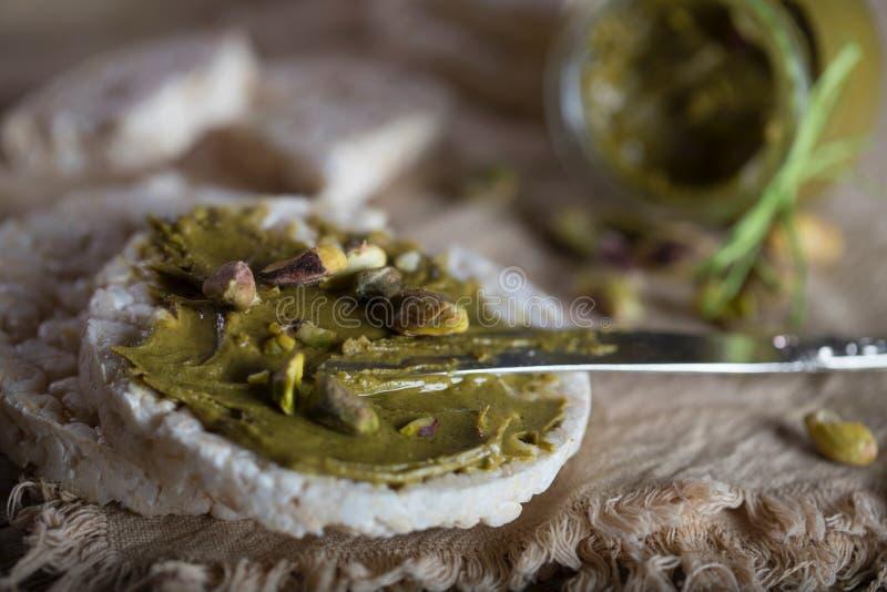 De boter van de pistachenoot die op een plak van rijstkn?ckebrood wordt afgeroomd stock afbeelding