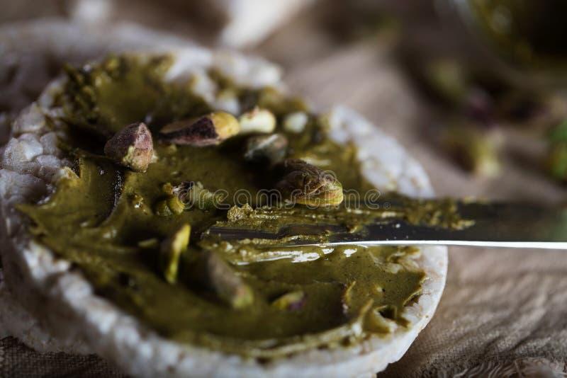 De boter van de pistachenoot die op een plak van rijstkn?ckebrood wordt afgeroomd stock foto's