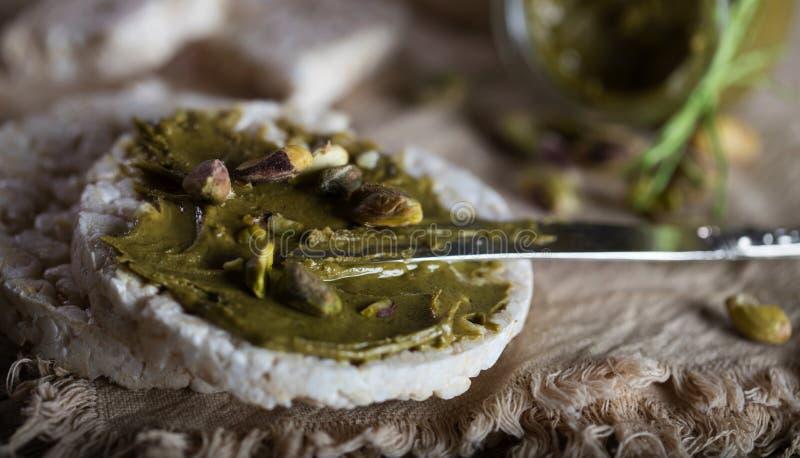 De boter van de pistachenoot die op een plak van rijstkn?ckebrood wordt afgeroomd royalty-vrije stock foto's