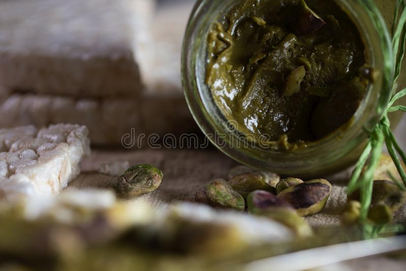 De boter van de pistachenoot die op een plak van rijstkn?ckebrood wordt afgeroomd royalty-vrije stock afbeelding