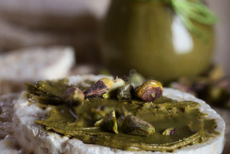De boter van de pistachenoot die op een plak van rijstkn?ckebrood wordt afgeroomd stock afbeeldingen