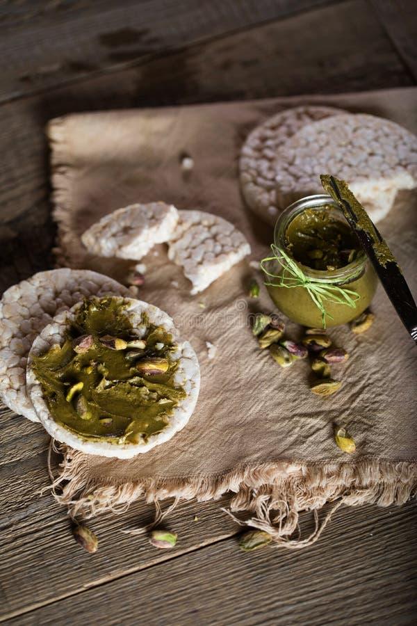 De boter van de pistachenoot die op een plak van rijstkn?ckebrood wordt afgeroomd royalty-vrije stock afbeeldingen