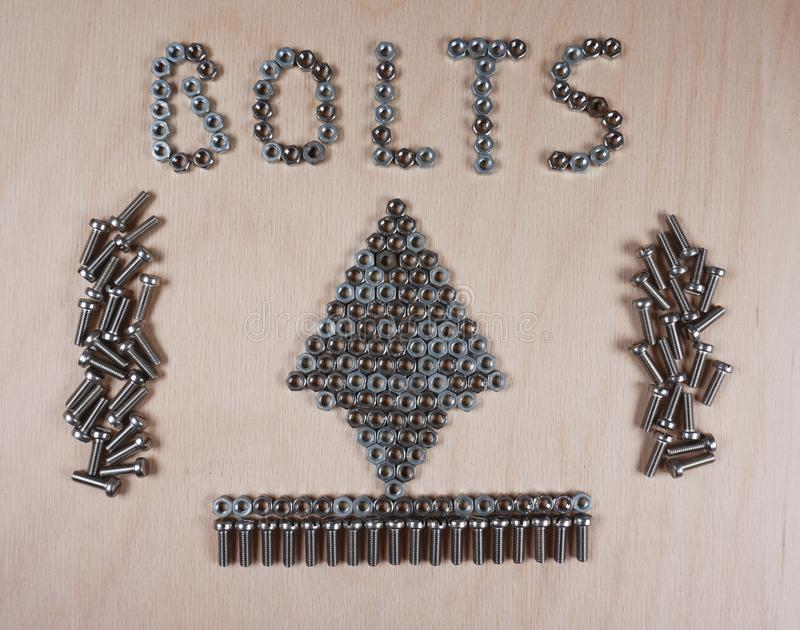 De bouten, noten, schroef, Kerstmisboom, vatten ge?soleerd op lichte houten achtergrond samen stock foto