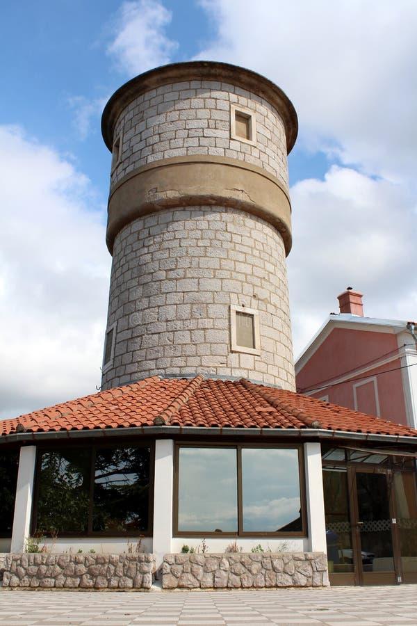 De bouw als middeleeuwse kasteeltoren met glasbodem en steenbouw wordt ontworpen naast familiehuis dat royalty-vrije stock afbeelding